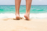 Women's beautiful legs on white sandy beach