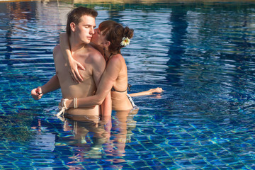 Young loving couple in the swimming pool