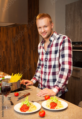 Handsome man cooking at home preparing pasta