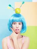 Creativity. Woman with Painted Blue Hairs and Apple on her Head