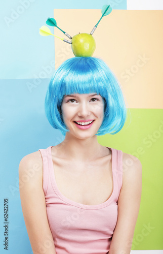 Precision. Amusing Woman in Blue Wig, Green Apple and Darts