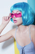 Individuality. Woman wears Blue Glossy Wig and Pink Glasses