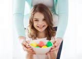 smiling girl and mother holding colored eggs