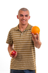 Studio shot of a young man who offers orange instead of red appl