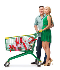 smiling couple with shopping cart and gift boxes