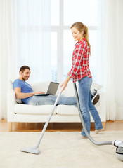 smiling woman with hoover and man with laptop