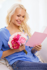 smiling woman with card and bouquet of flowers
