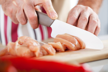 Senior Male Hands Cutting Chicken filet