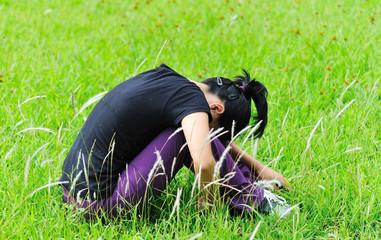 depress woman sit in grass
