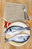 Gilt-head bream fish on wooden background. Mediterranean tavern,