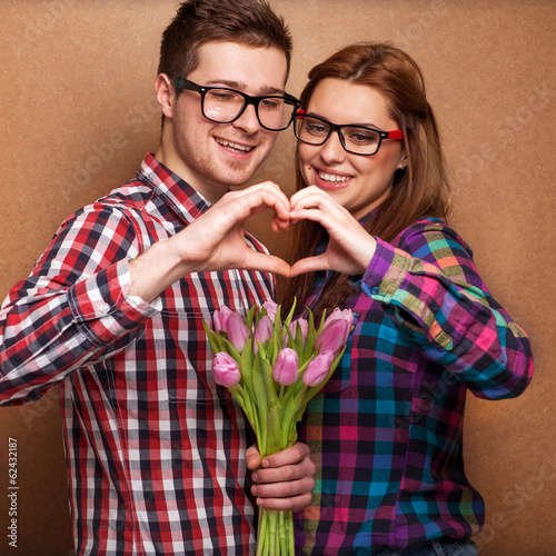 Young couple in love make a heart and hands are holding bouquet