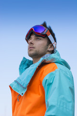 Friendly attractive skier or snowboarder against blue sky