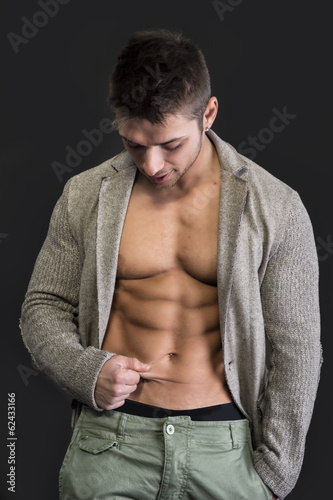 Muscular and fit young man pinching his stomach skin