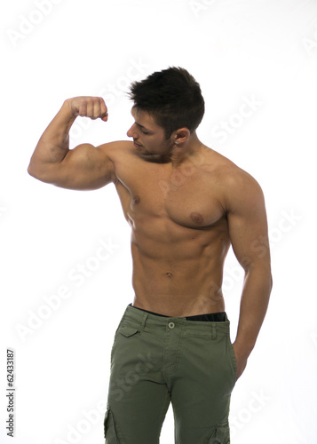 Muscular shirtless young man flexing and looking at his bicep