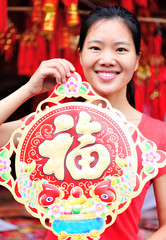 young asian woman hold a chinese fook wishing a happy new year