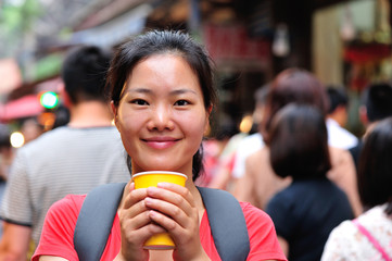 asian woman holding cup of coffee at street in xian