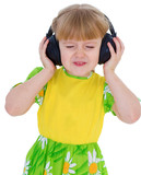 Very musical little girl having fun listening to music through t