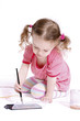 Funny little girl with ponytails drawing with waterolors