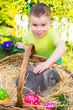Kind streichelt Osterhasen im Korb mit Eiern