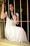Young woman looking from behind the bars