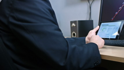 Hand swiping through business graphs on tablet device