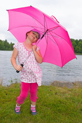 Portrait of smiling young girl with pink umbrella
