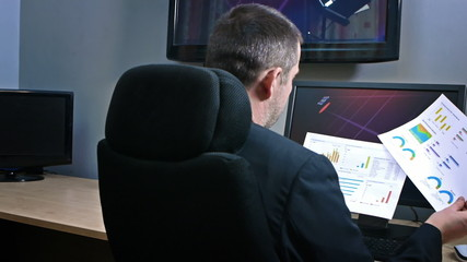 Businessman reading reports surrounded by screens
