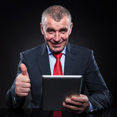 old man working on tablet making the ok sign
