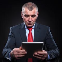 senior business man reading on tablet pad computer