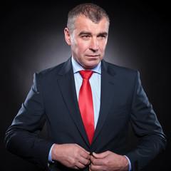 attractive mature elegant man unbuttoning his suit ad looks away
