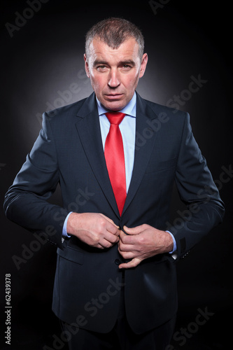 attractive senior business man buttoning his coat