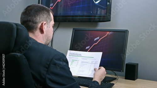 Businessman receiving reports and looking at graphs