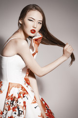 young beautiful asian brunette in gorgeous dress touching hair.