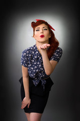 Pin up girl leaning forward and blowing a kiss