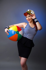 Pin up model in sailor costume holding a beach ball