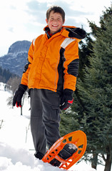 boy with winter clothing and snowshoes for a long walk in the sn