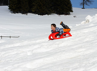 boy comes down with the red sled in the mountains on the snow