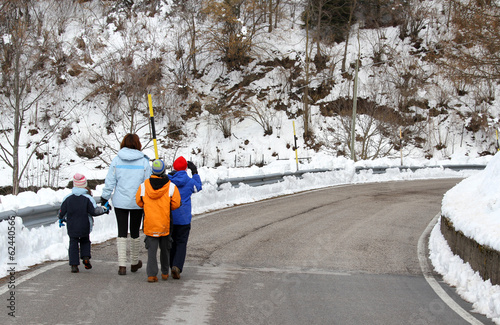 young family with three children walking on snow-covered road in