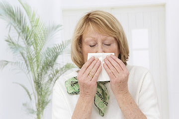 Elderly blond woman has flu