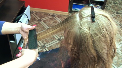 hairdresser spray water on woman long hair trims the hair tips