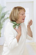 Elderly woman has flu and sneezing