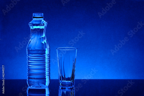 Water in plastic bottle with glass blue background