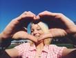 Mädchen formt Herz mit Fingern