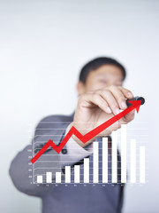 business person drawing an arrow to show upward trend