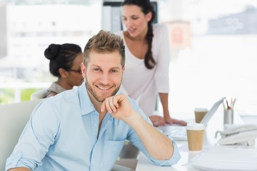 Handsome man smiling at camera while colleagues talk at desk