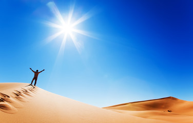 adult white man standing on a sand dune and holding arms up