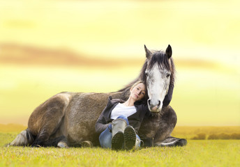 girl and gray Arabian horse lie at sunset on summer pasture