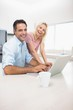 Portrait of cheerful couple using laptop in kitchen