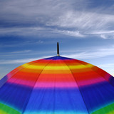 Rainbow colored umbrella top with blue sky above it
