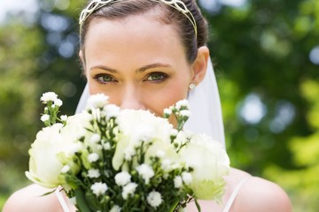 Bride peeking over bouquet in garden